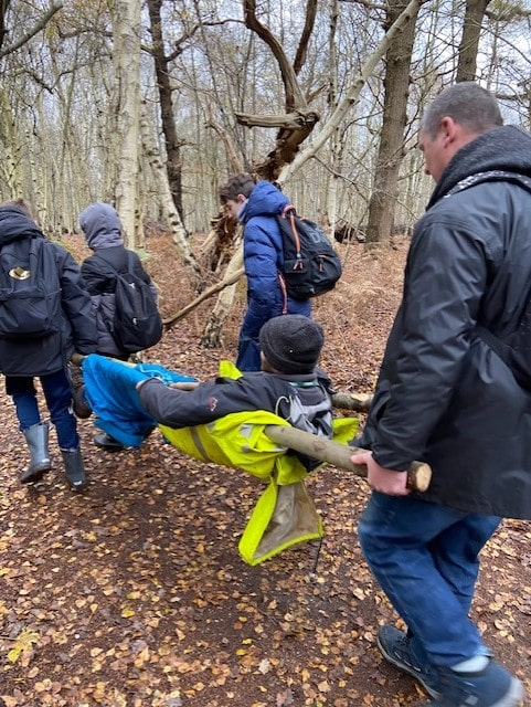 Thrive students in the woods carrying male on stretcher. The Mix Stowmarket