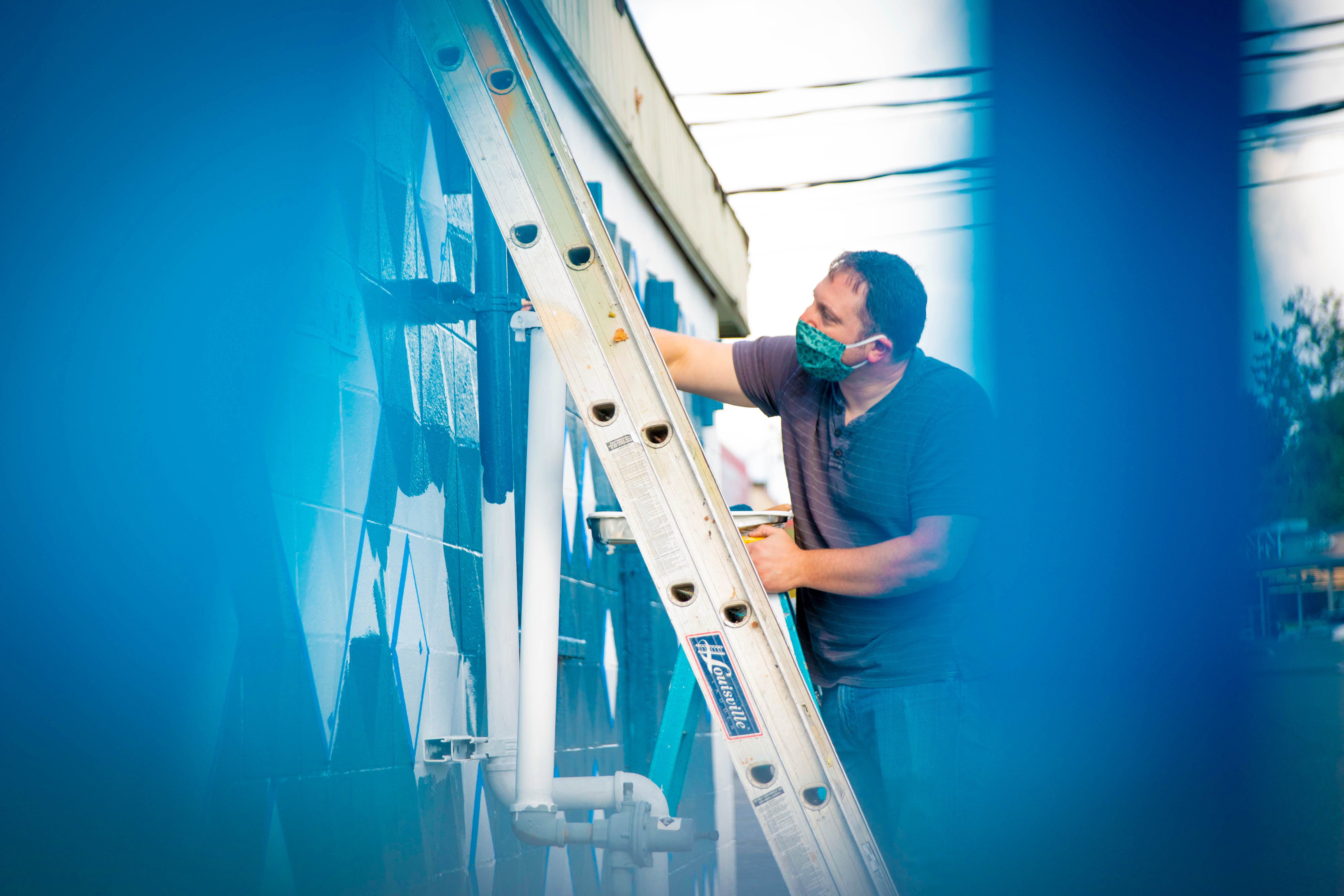 Man on ladder painting mural