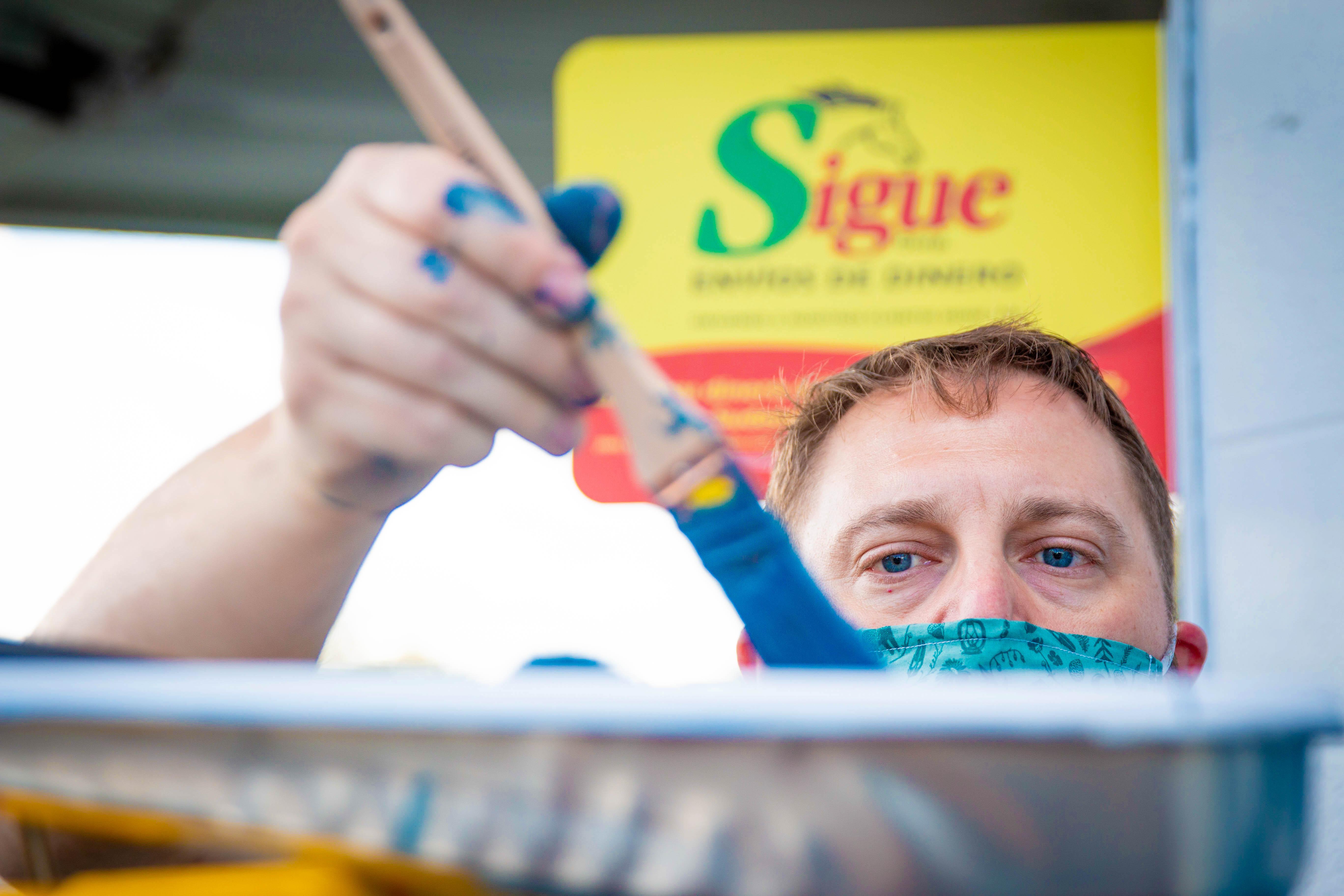 Man applying paint to paintbrush