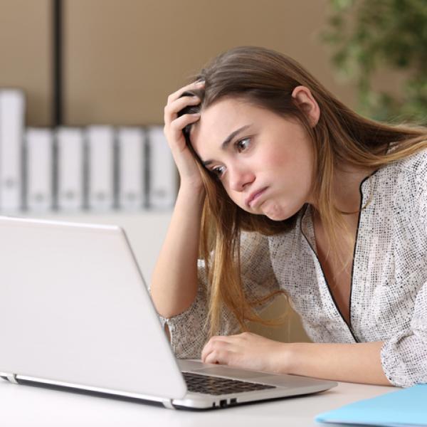 """Persona que piensa: """"no sé qué estudiar"""" frente al ordenador"""