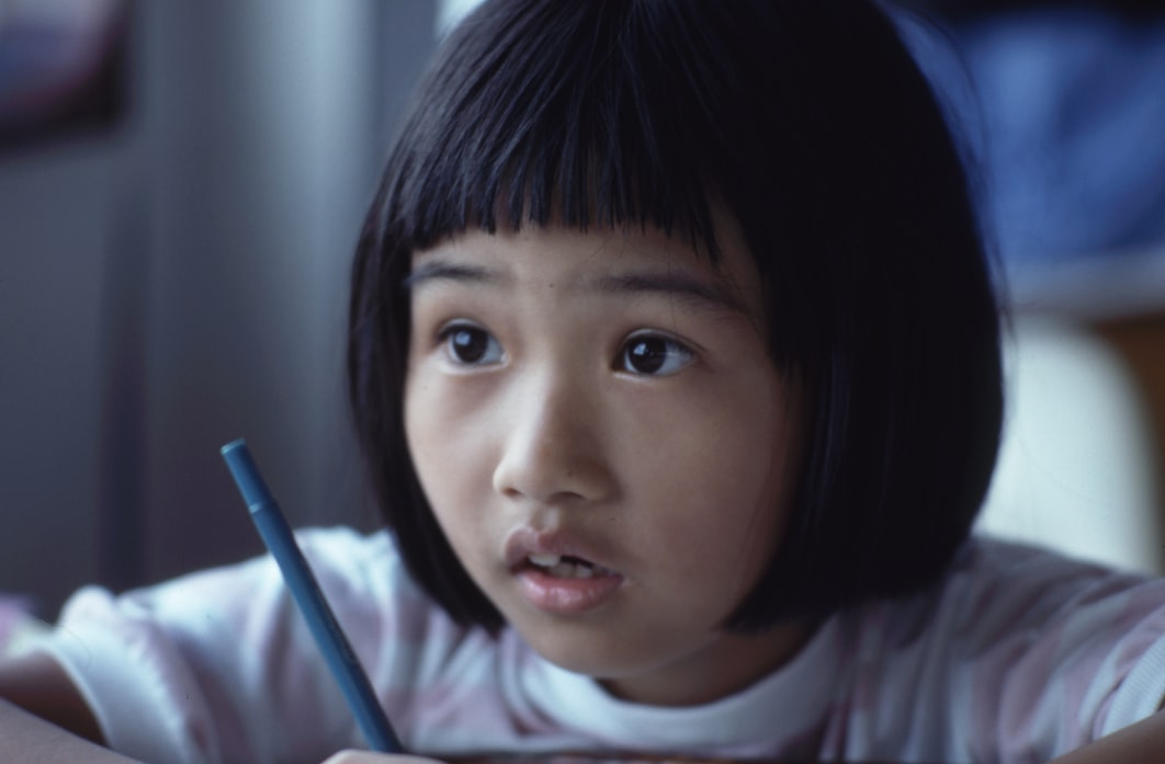 an asian young girl at school having trouble understanding the lesson