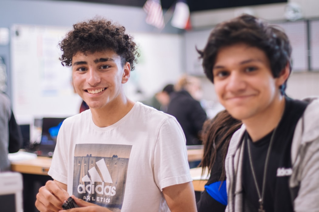 2 young male students next to each other at school looking happy at the camera