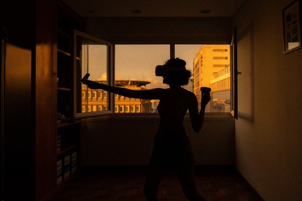 A young woman exercising in her living room using a virtual reality headset, in a dark lit scene