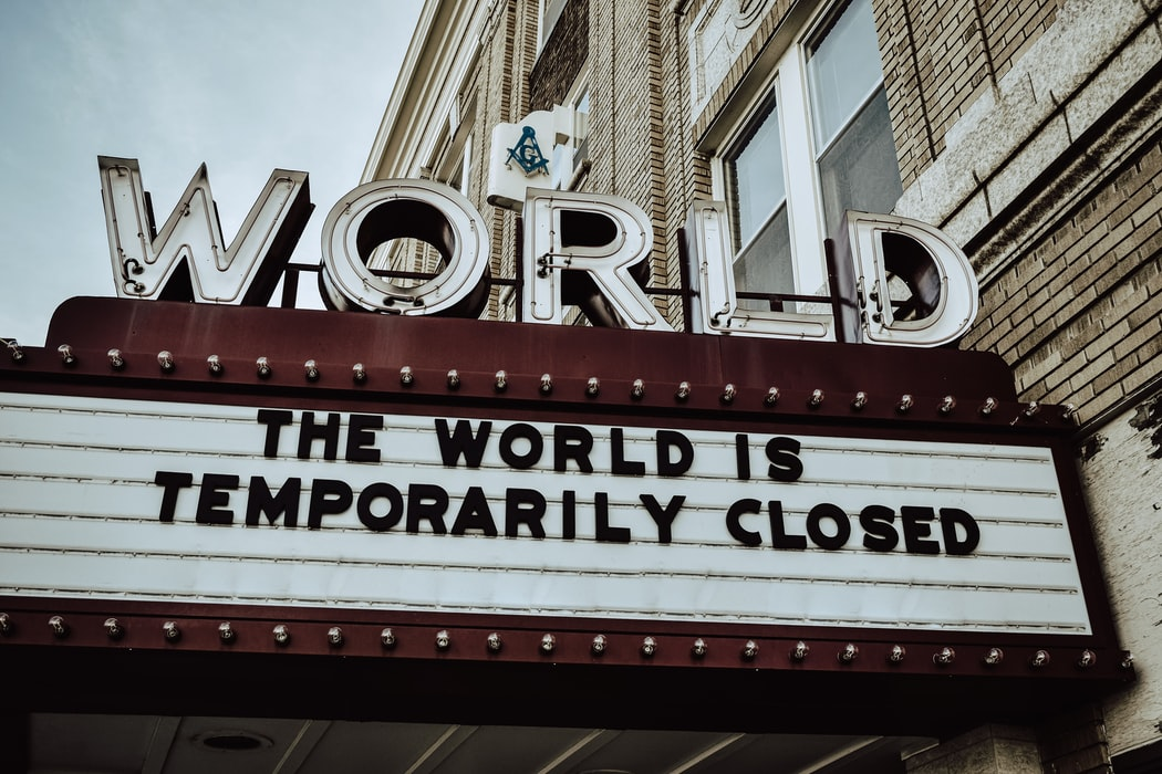 """a theater sign showing the phrase """"the world is temporarily closed"""""""