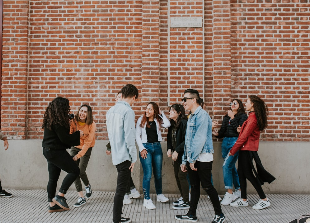 A group of young adults in front of a brick wall interacting and having fun