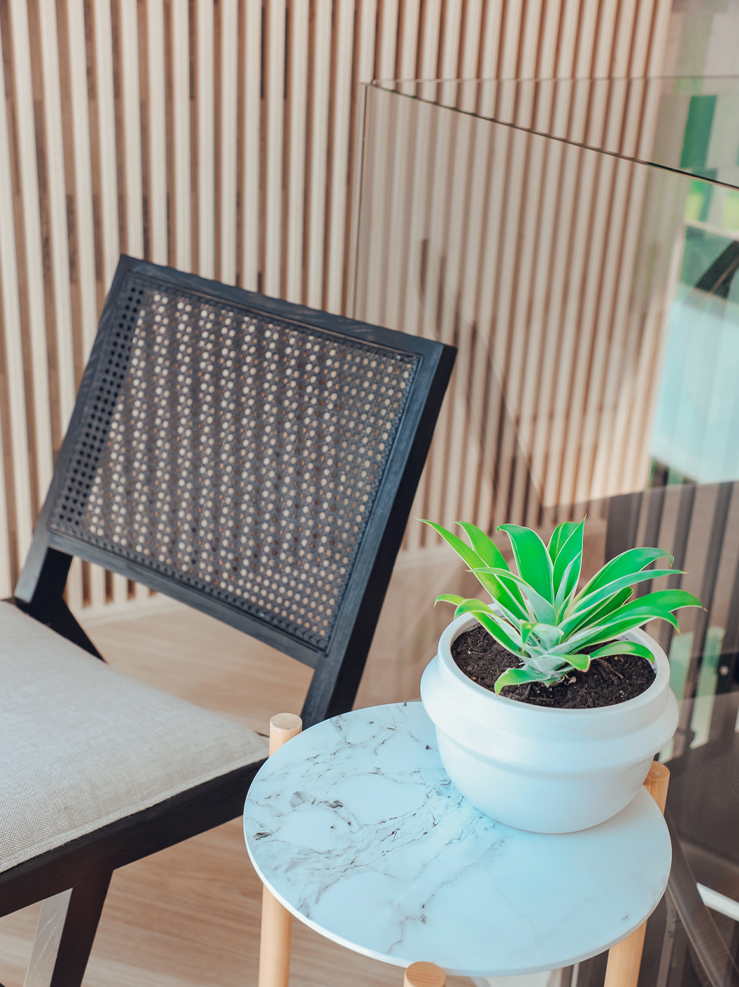 A chair next to a table with a pot plant.