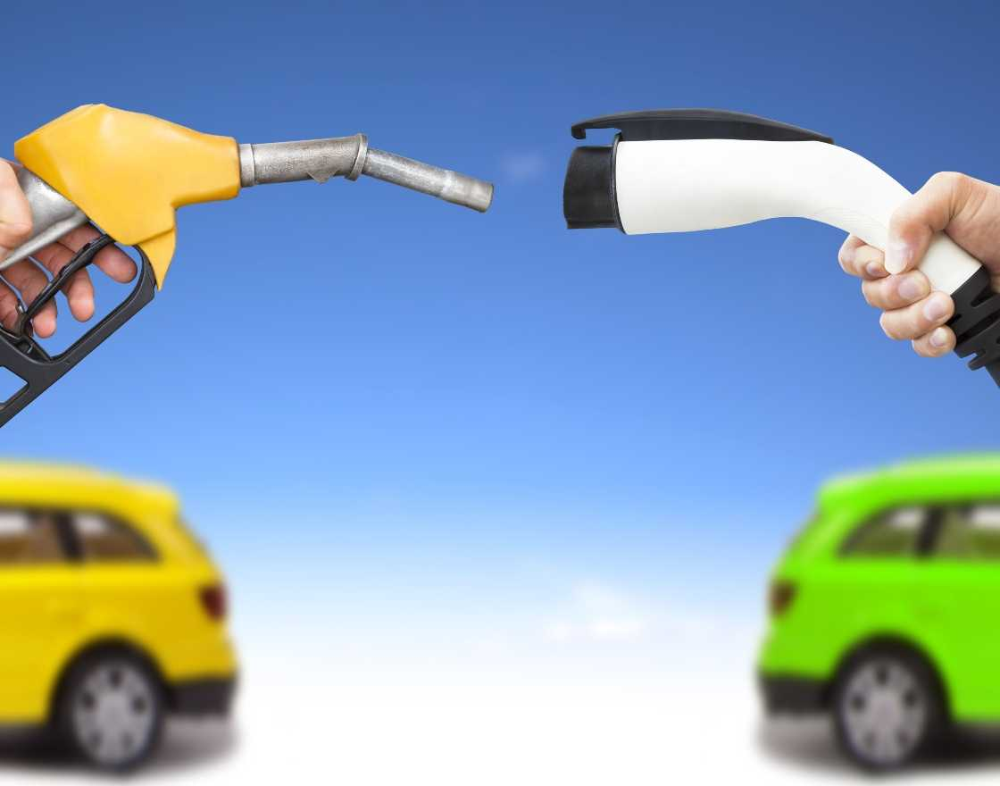 Electric vehicle charging plug held up next to a oil gas pump nozzle