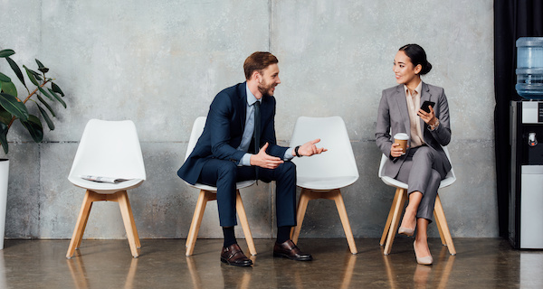 Man and woman having water cooler conversation in office