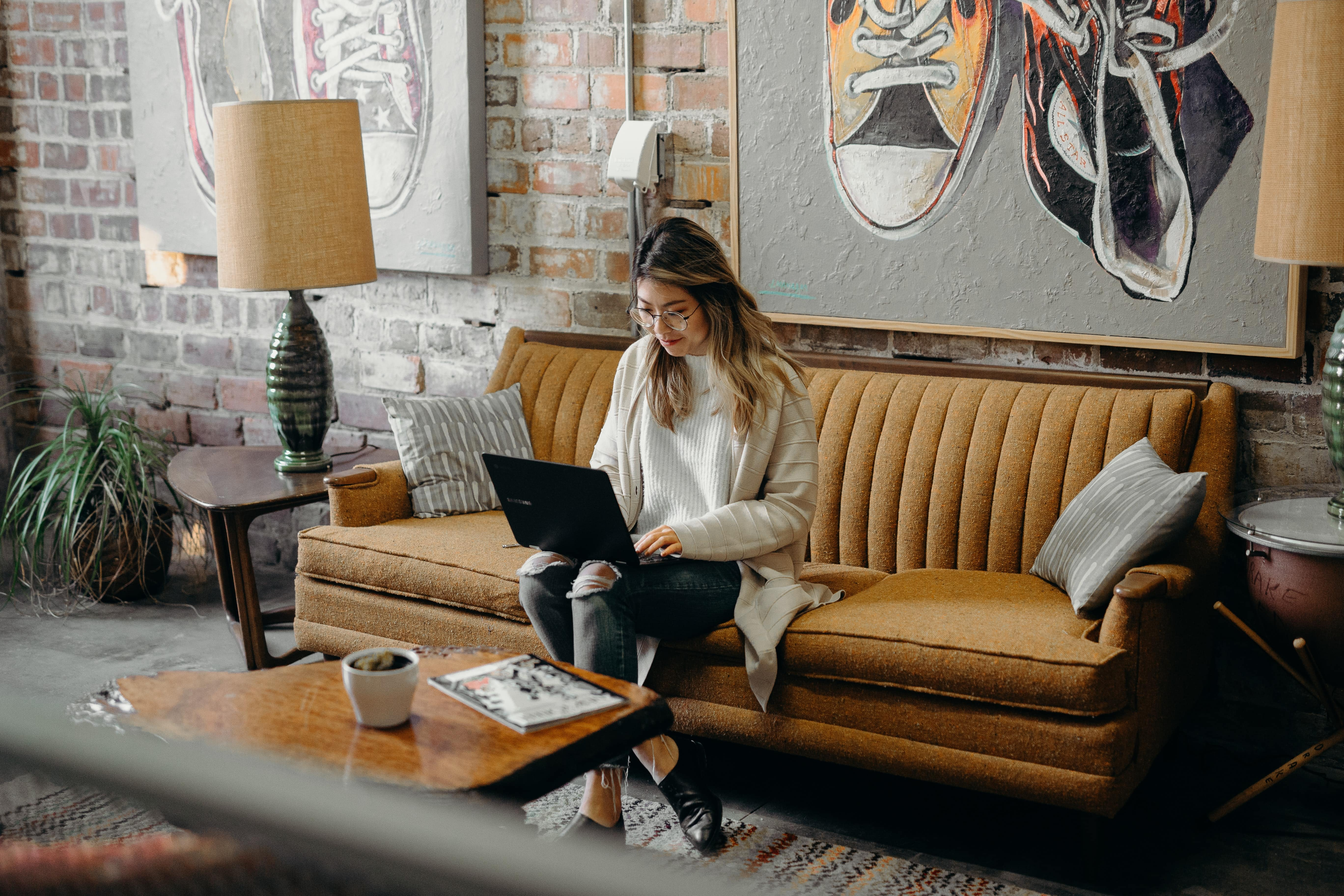 Woman sitting on her sofa with a laptop