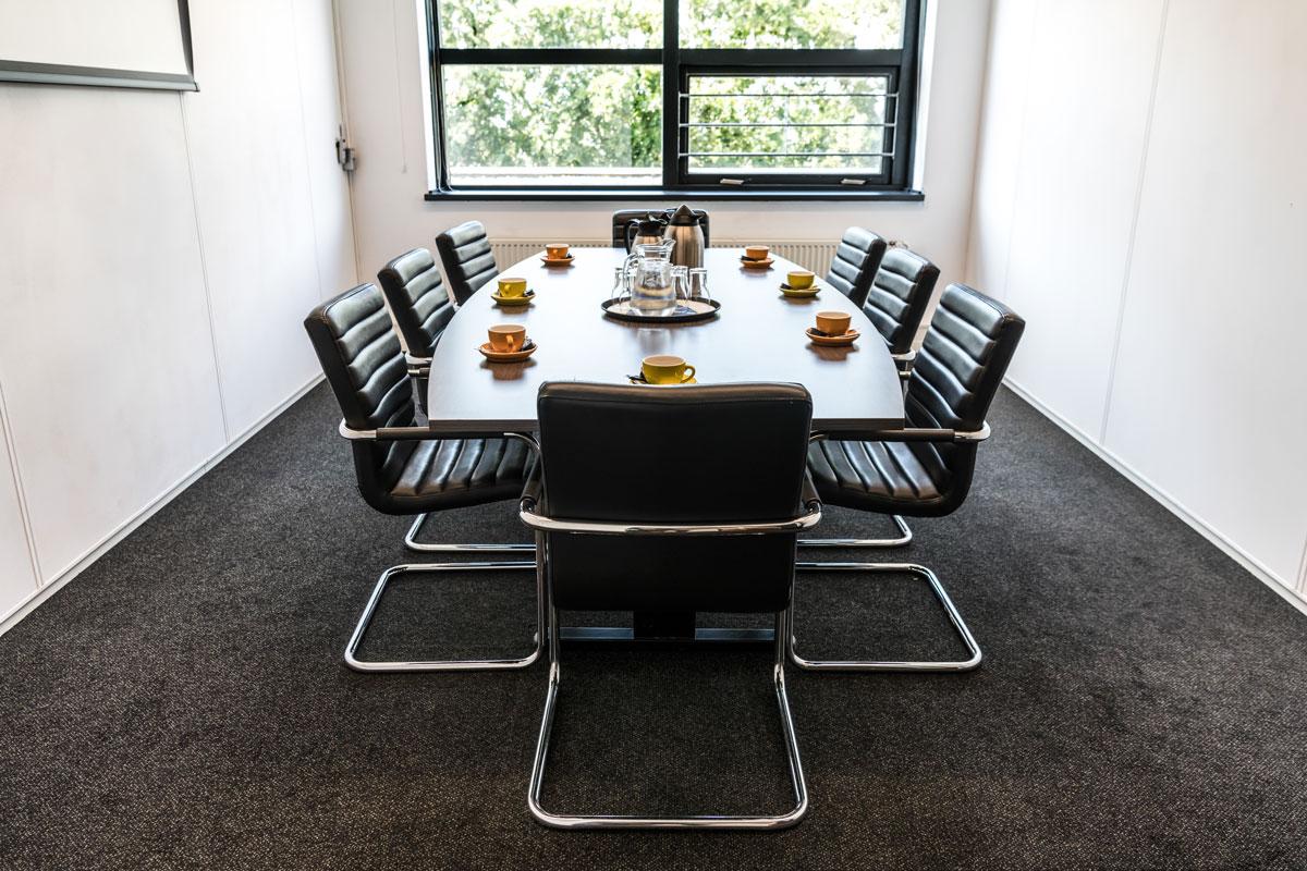 Interieur foto van een boardroom met 1 grote tafel en 8 stoelen