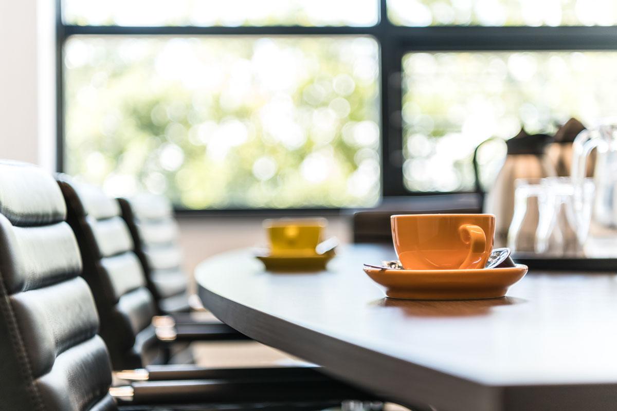 Ingezoomde foto van 2 kopjes op tafel in een boardroom