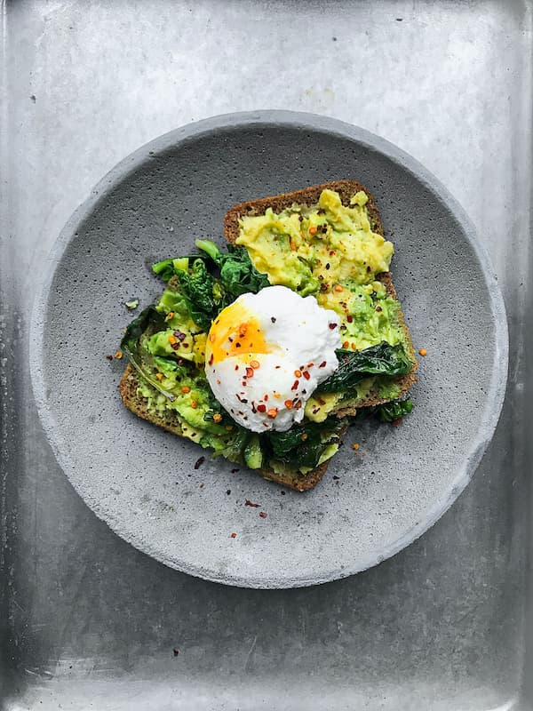 smashed avocado on toast served with a poached egg