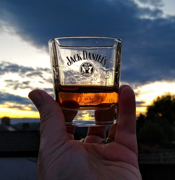 a hand holds a glass of Jack Daniel's whiskey up to the sky