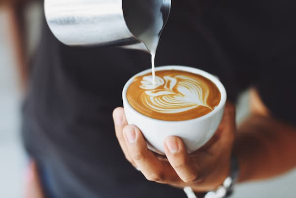 a barista pours latte art in the shape of a tulip