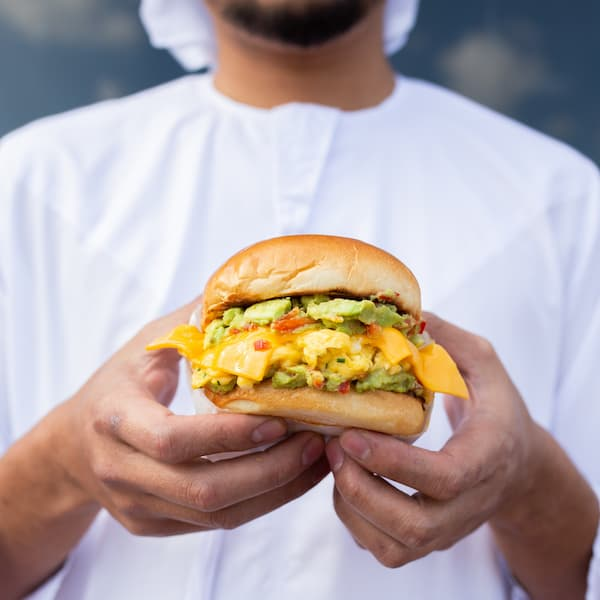 a man in a white t shirt holds out a burger with avocado and cheese