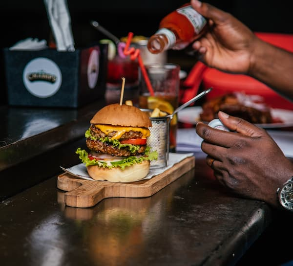 tomato ketchup is poured over a tripe stacked burger served in a restaurant bar