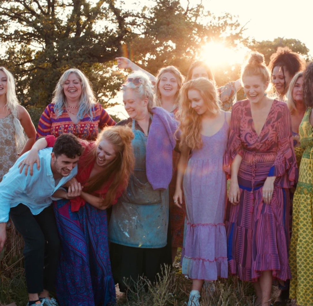 A group shot of the Ian Snow team all dressed in colourful clothing with a sun bloom behind them.
