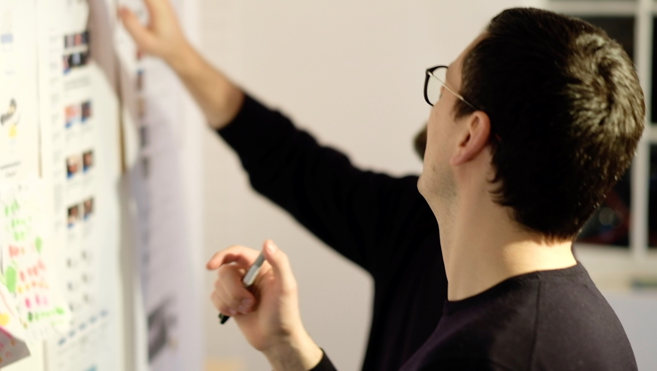 Two professional men working through a design solution in front of a whiteboard.