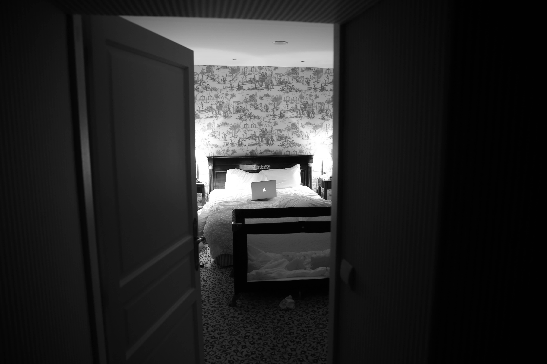 Photographie d'une chambre à coucher, un ordinteur portable est posé sur lit