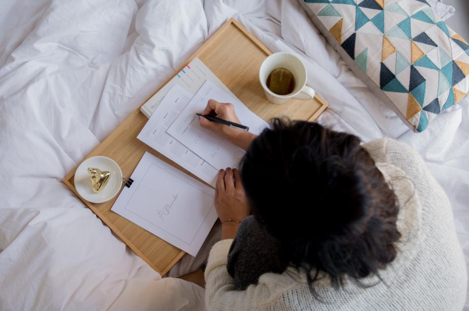 Femme qui écrit, installée confortablement dans son lit, avec une tisane.