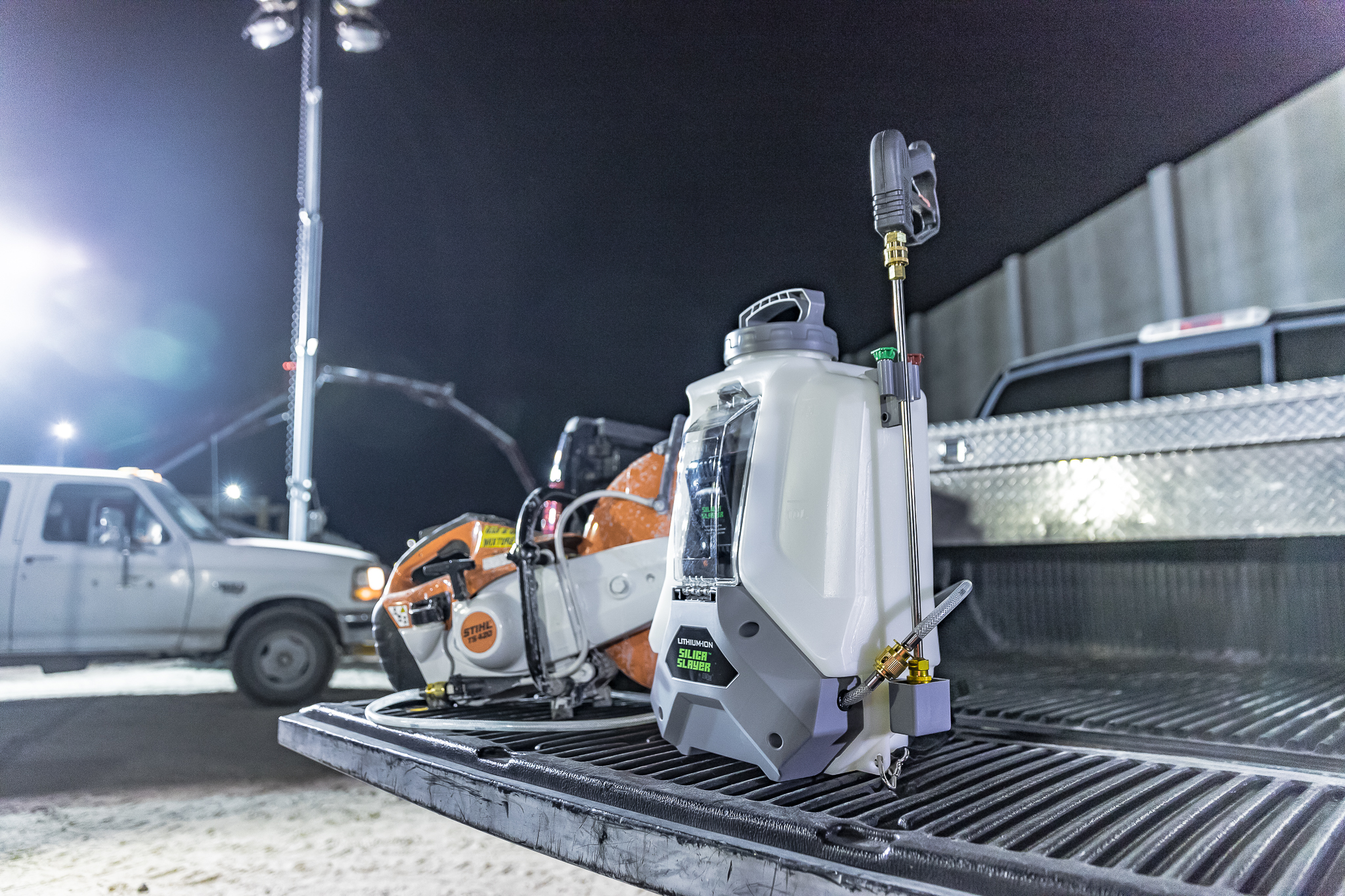a 4-gallon Silica Slayer battery powered backpack sprayer sitting on the back of a pickup truck at night next to a cut saw