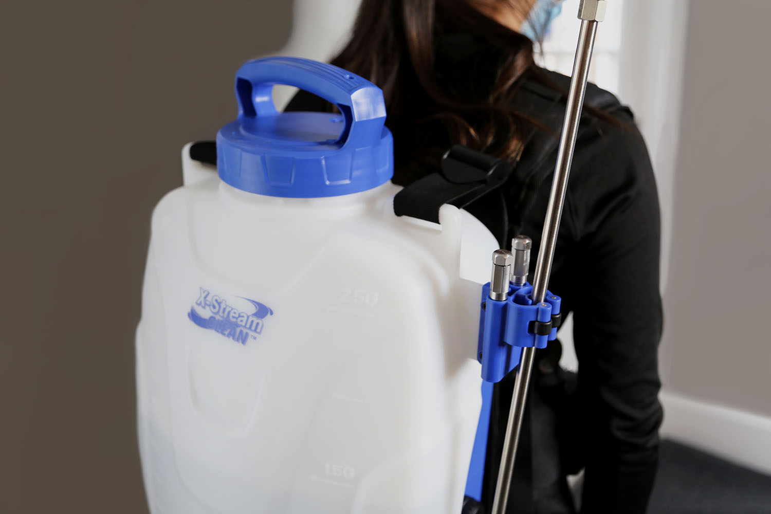 woman wearing an X-Stream Clean Microburst battery powered backpack sprayer in a bathroom