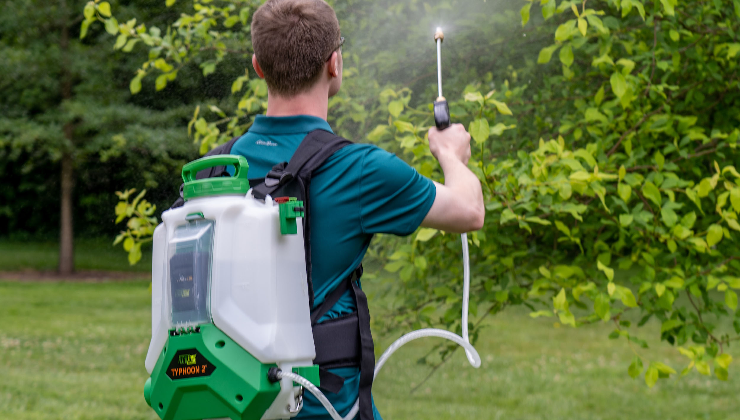 Man with FlowZone battery powered backpack sprayer misting a tree with water