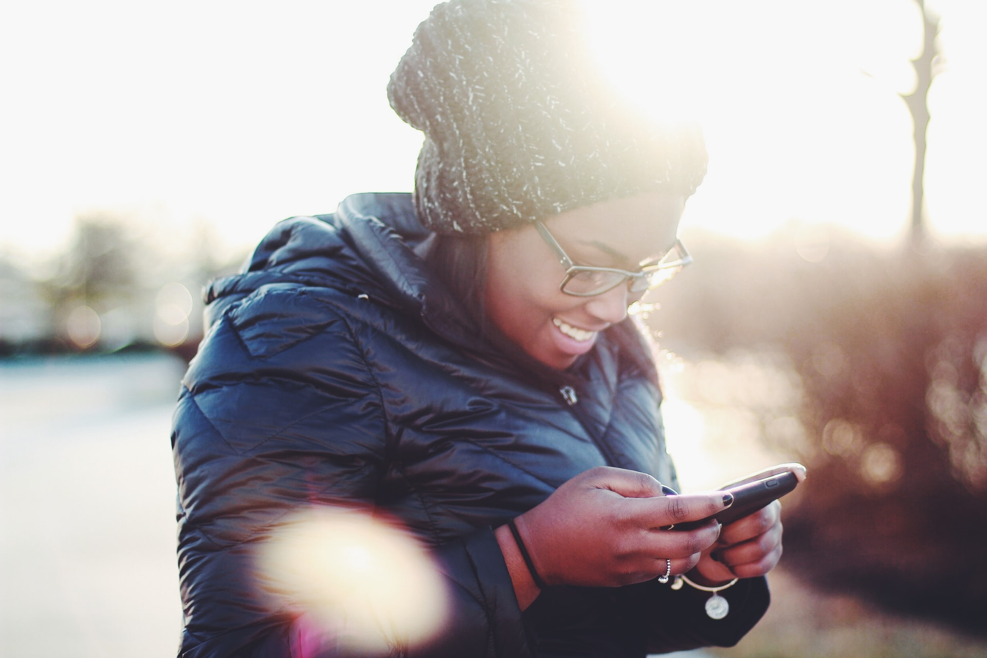 A photo of a person in a stocking cap and warm coat smiling while using their phone
