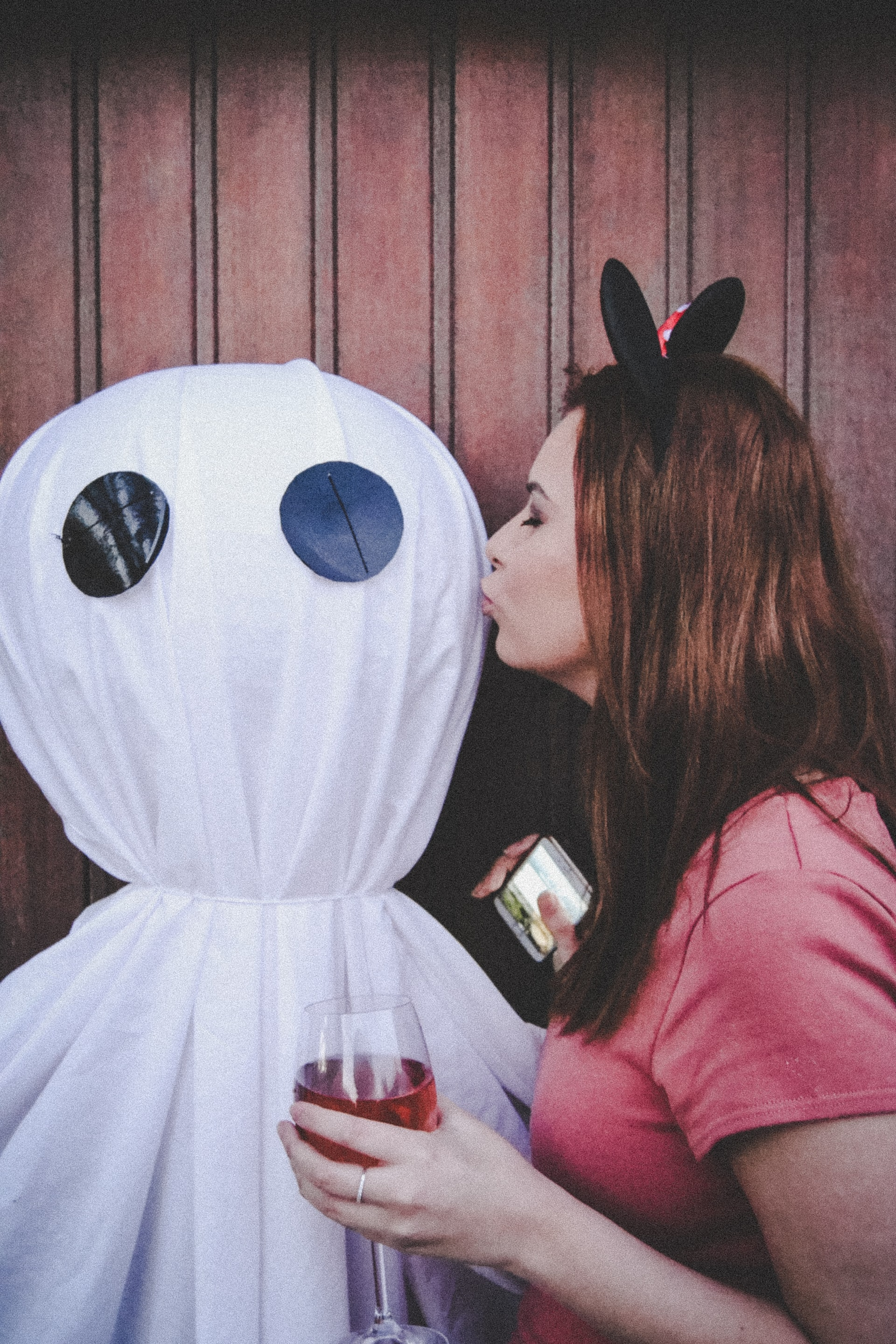 A photo of someone kissing a stuffed ghost on the cheek, assuming ghosts actually have cheeks.