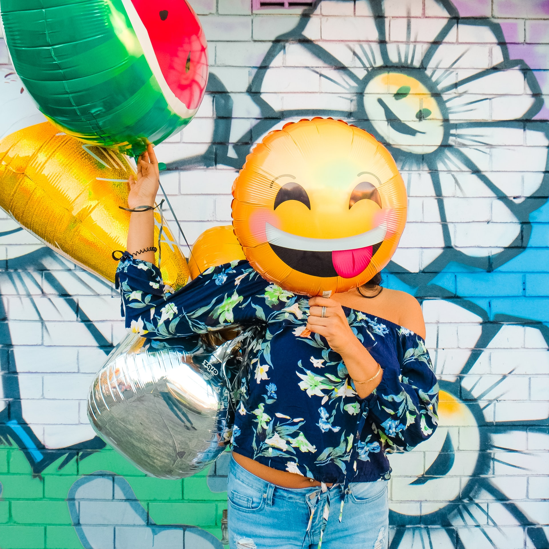 An image of someone holding balloons in their outstretched right hand. Their left hand holds a yellow smiley face balloon in front of their face
