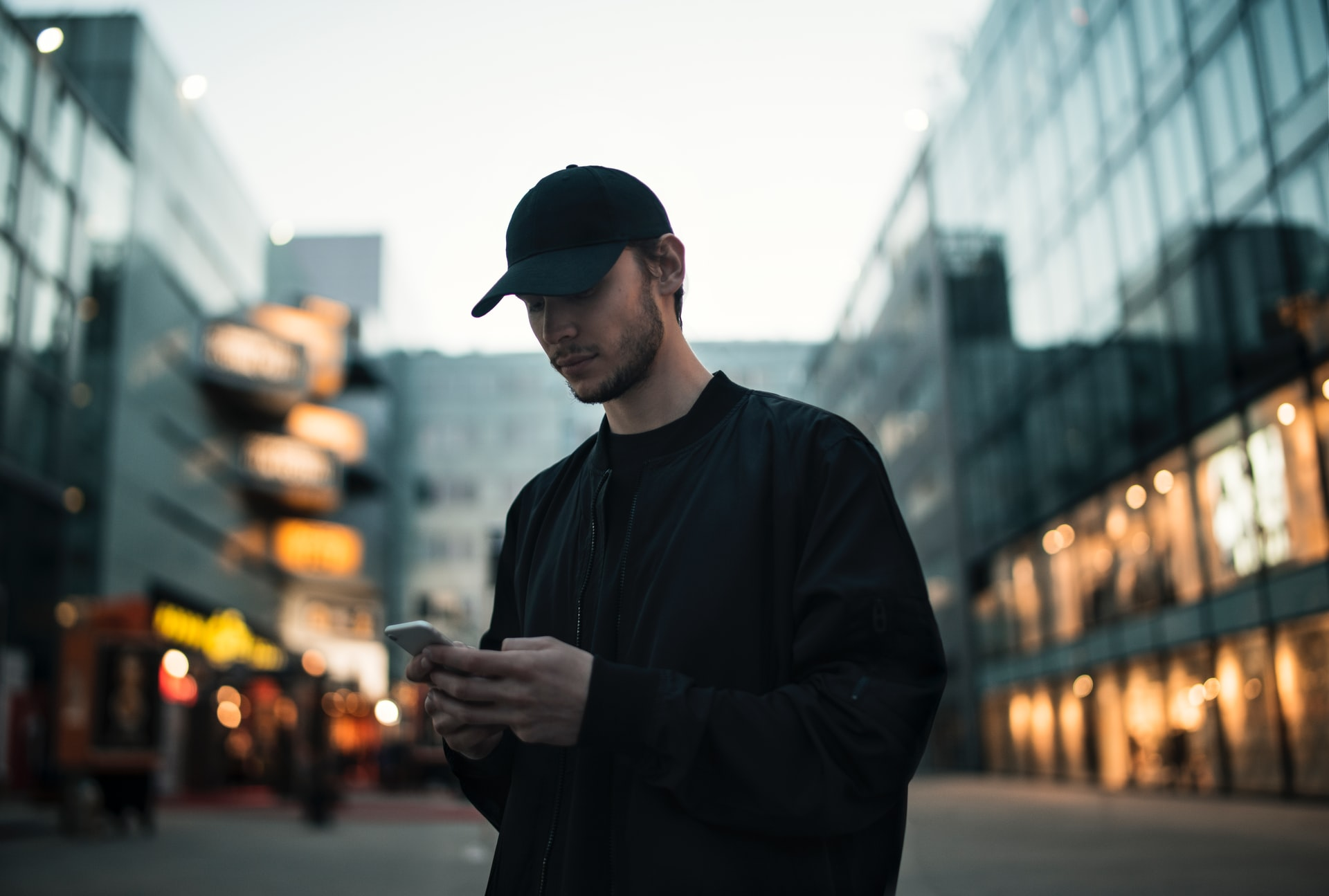 An image of a person wearing all black in a city using a cell phone
