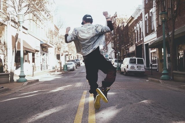 An image of a person jumping and clicking their heels in the middle of the street