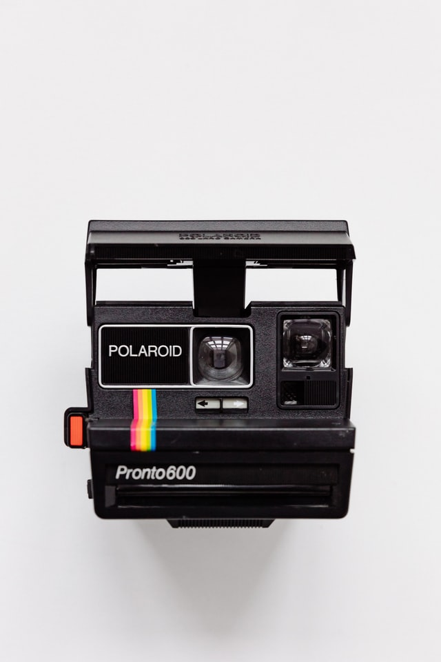 An image of a polaroid camera on a white backdrop