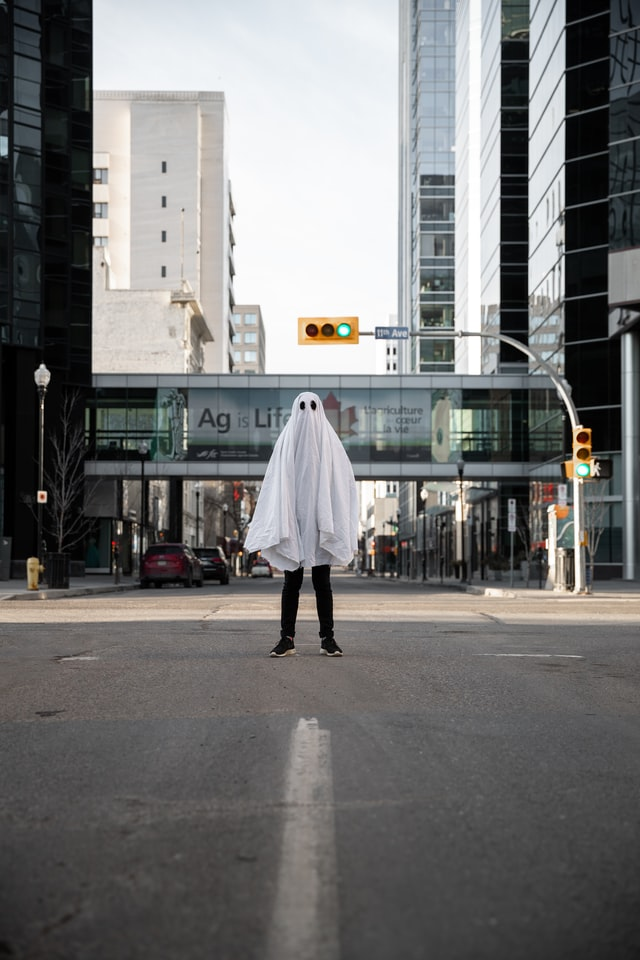 An image of a person dressed as a ghost in the middle of the street in a city