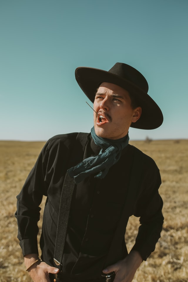 A portrait of a person standing in a field dressed in western clothing wearing a cowboy hat with a piece of straw in their mouth