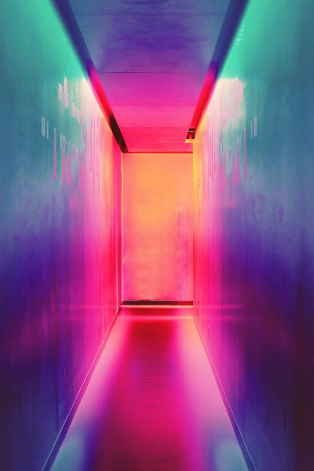 A reflective hallway lit with many different colored lights.