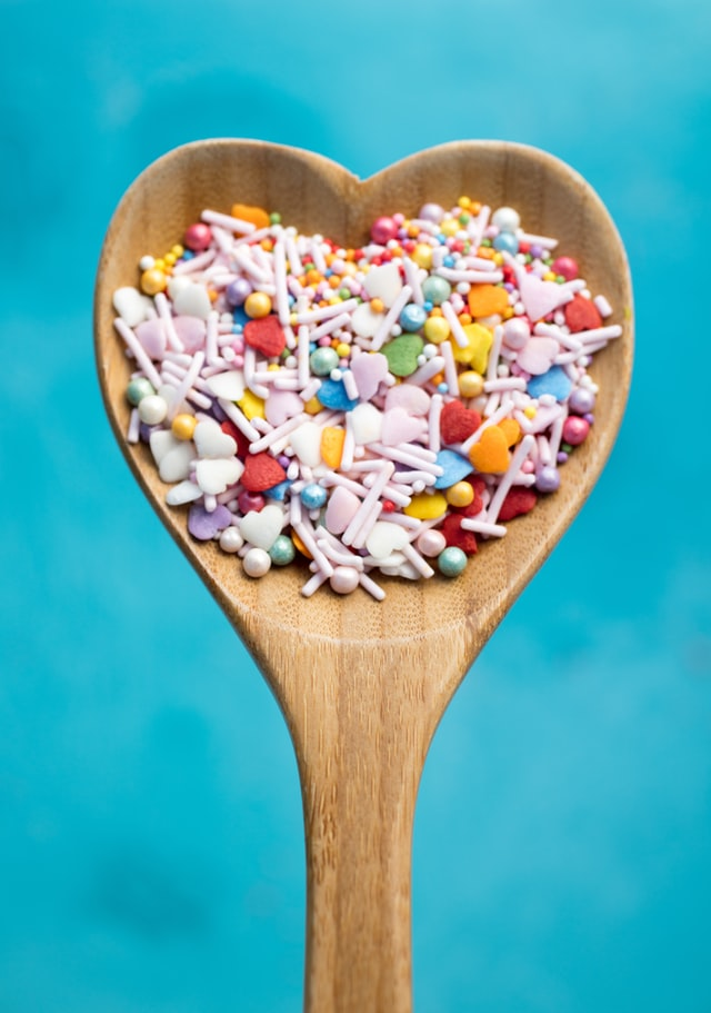 A wooden, heart-shaped spoon with assorted sprinkles in it against a blue backdrop.