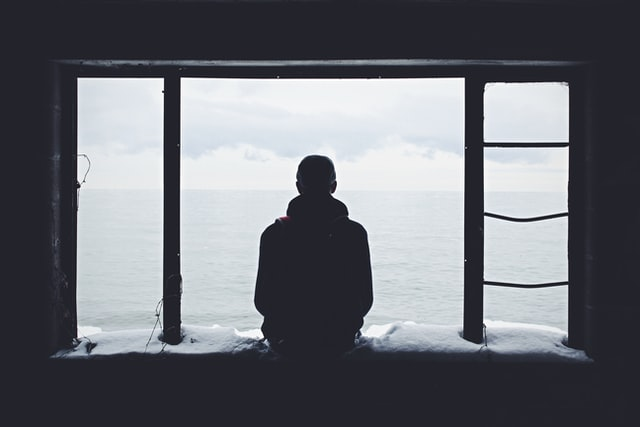 Black and white photo of a silhouette of a person looking out a window.