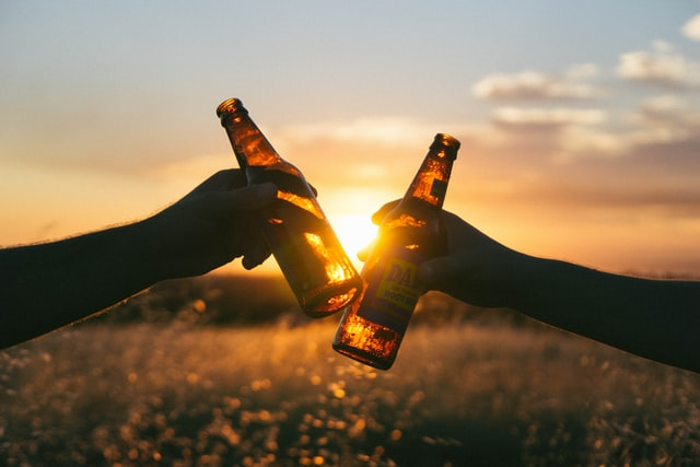 Two people out of frame clinking beer bottles with the sunset in the background.