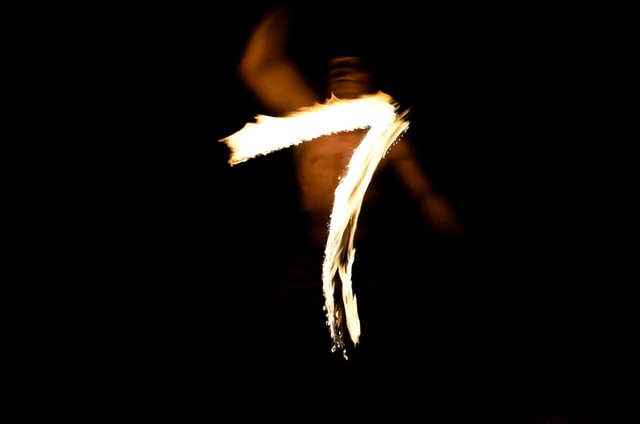 A long exposure shot of a flame being moved to create the number seven.