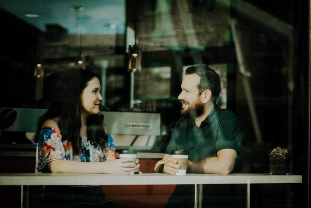 A couple drinking coffee at a counter near a window.