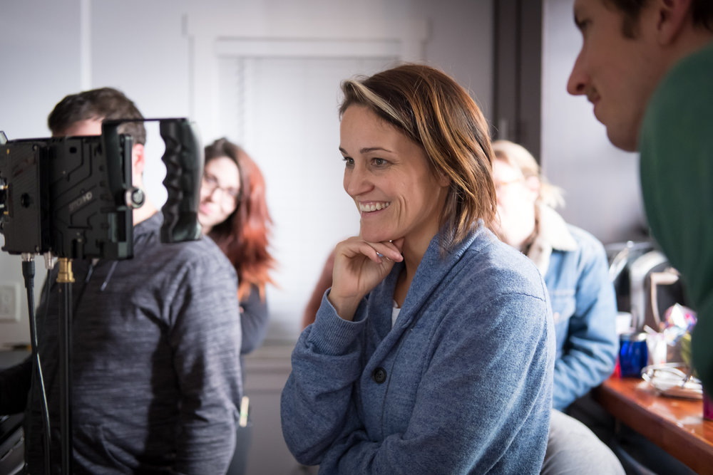 Luvia Petersen smiling behind a camera directing.