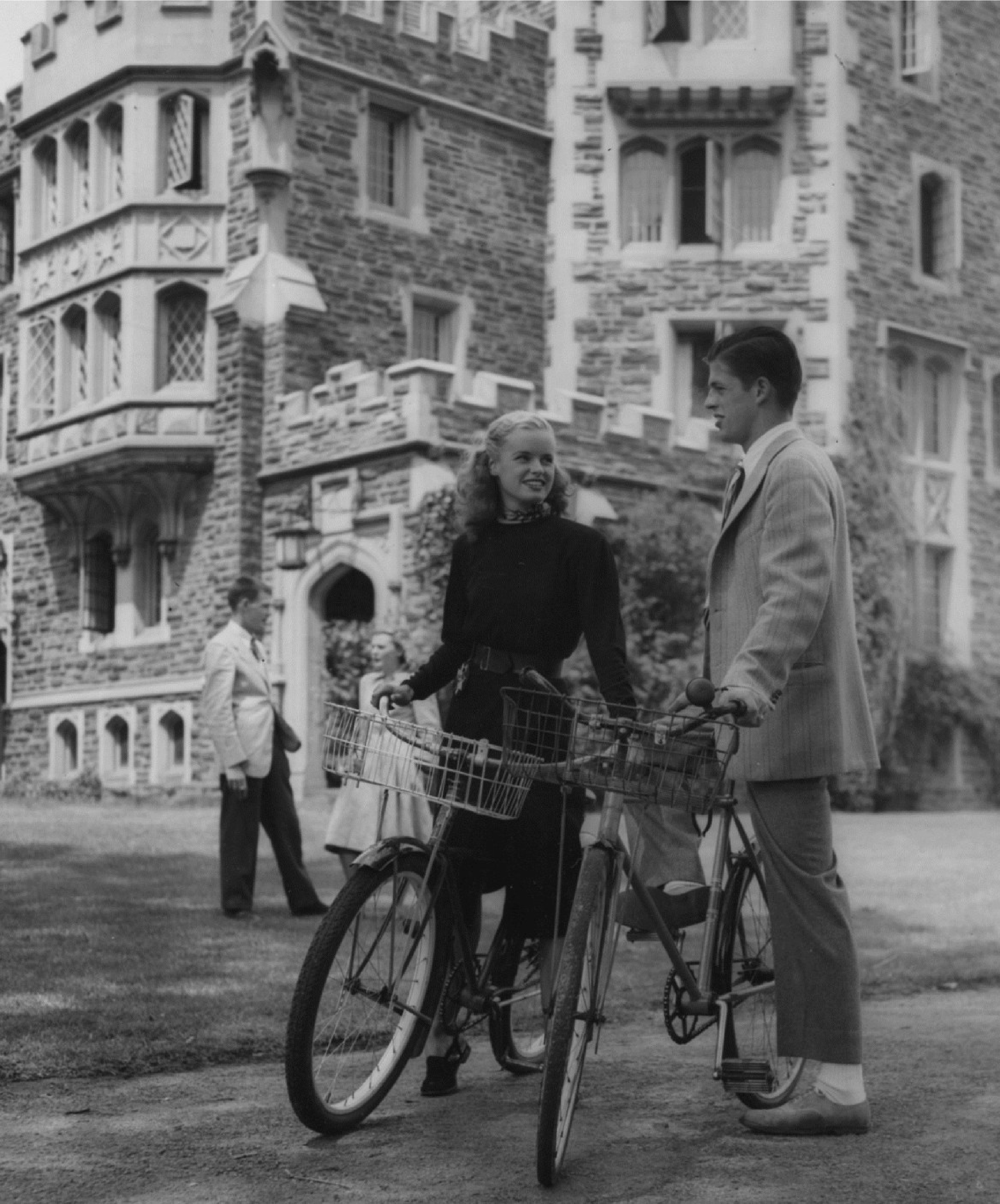 Princeton couple in formal attire standing by their bicycles in 1946.