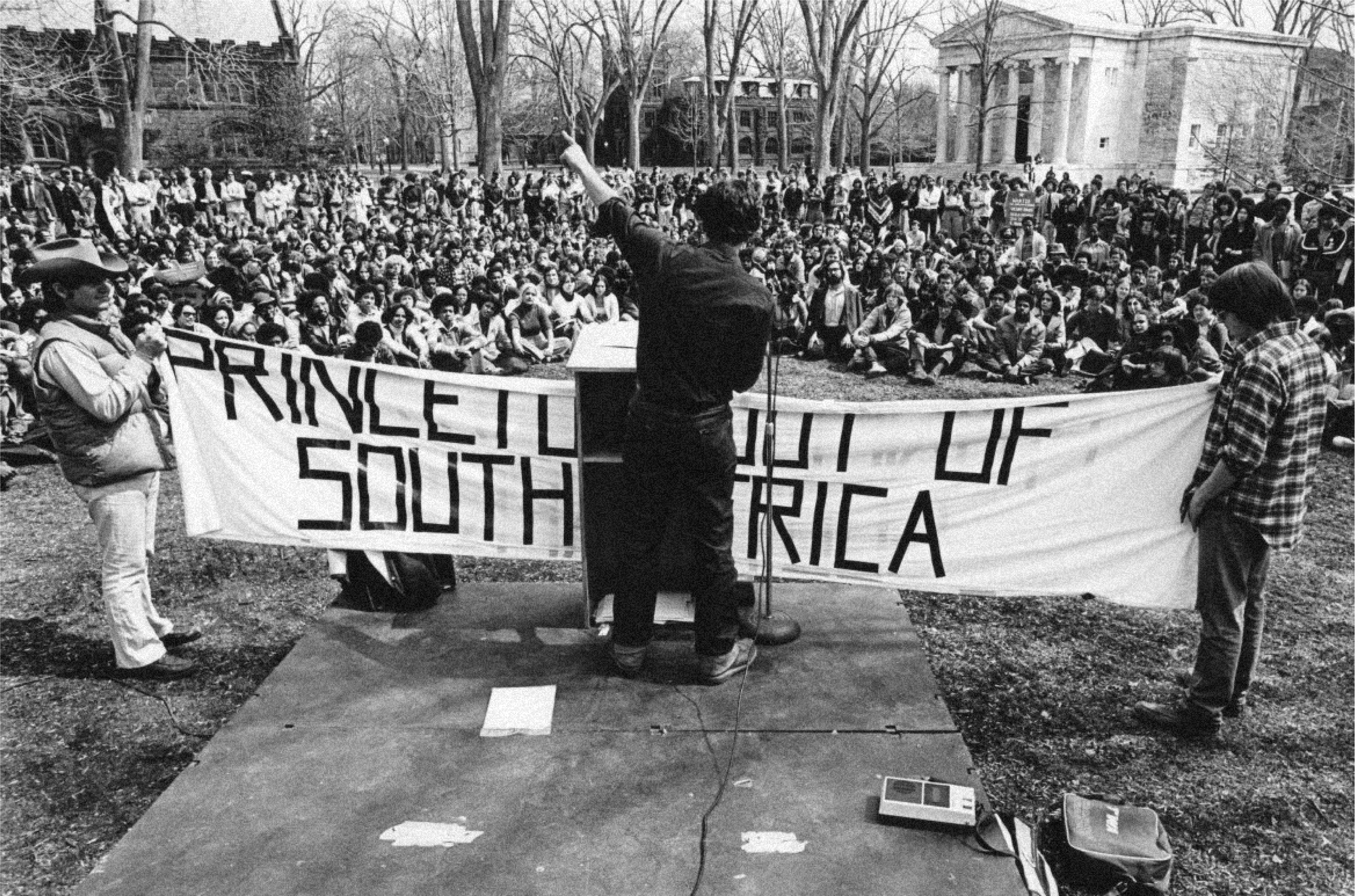 """Activists with a """"Princeton Out of South Africa"""" banner speak to a crowd of hundreds of students on Cannon Green in 1978."""