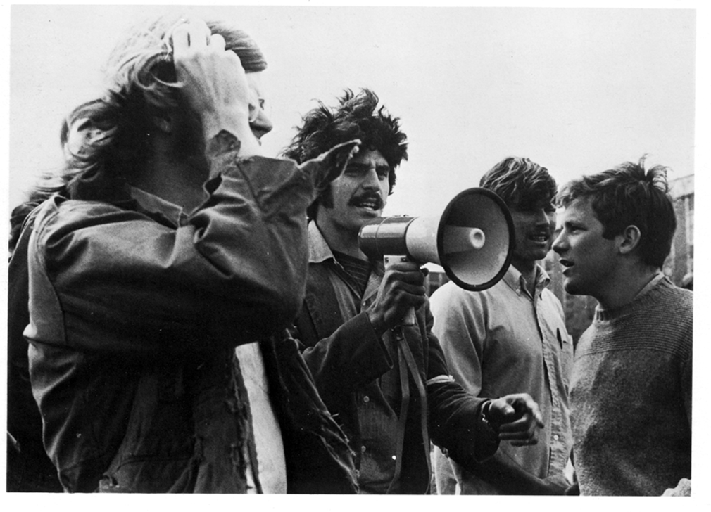 Students standing together with a megaphone during a protest.