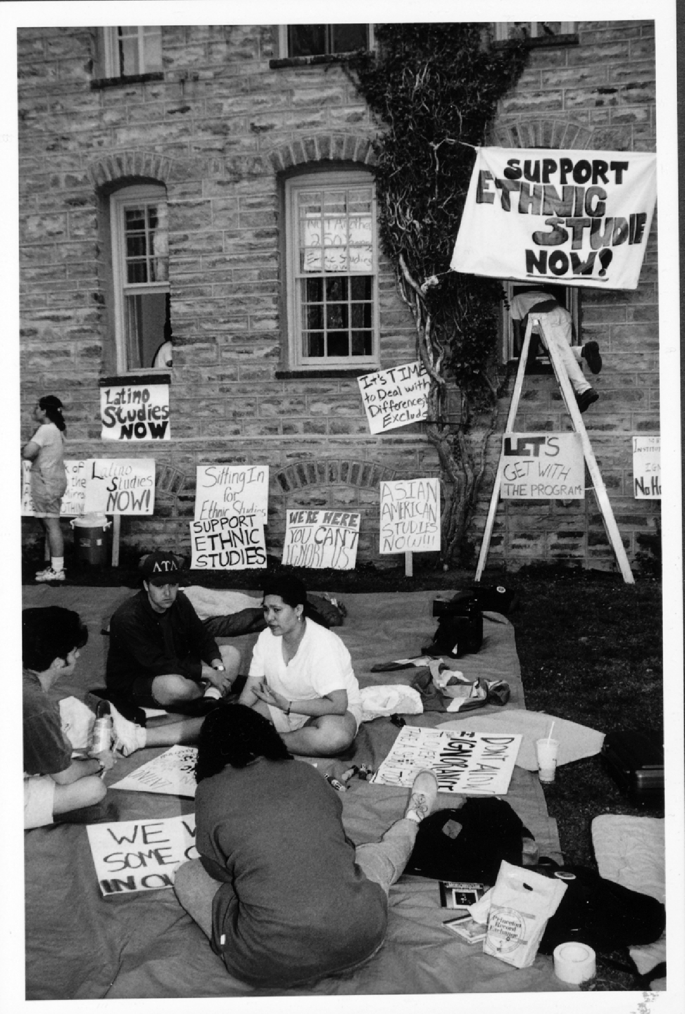 """Students sitting in a group during a 1995 protest for ethnic studies, with signs such as """"Support Ethnic Studies Now!"""""""