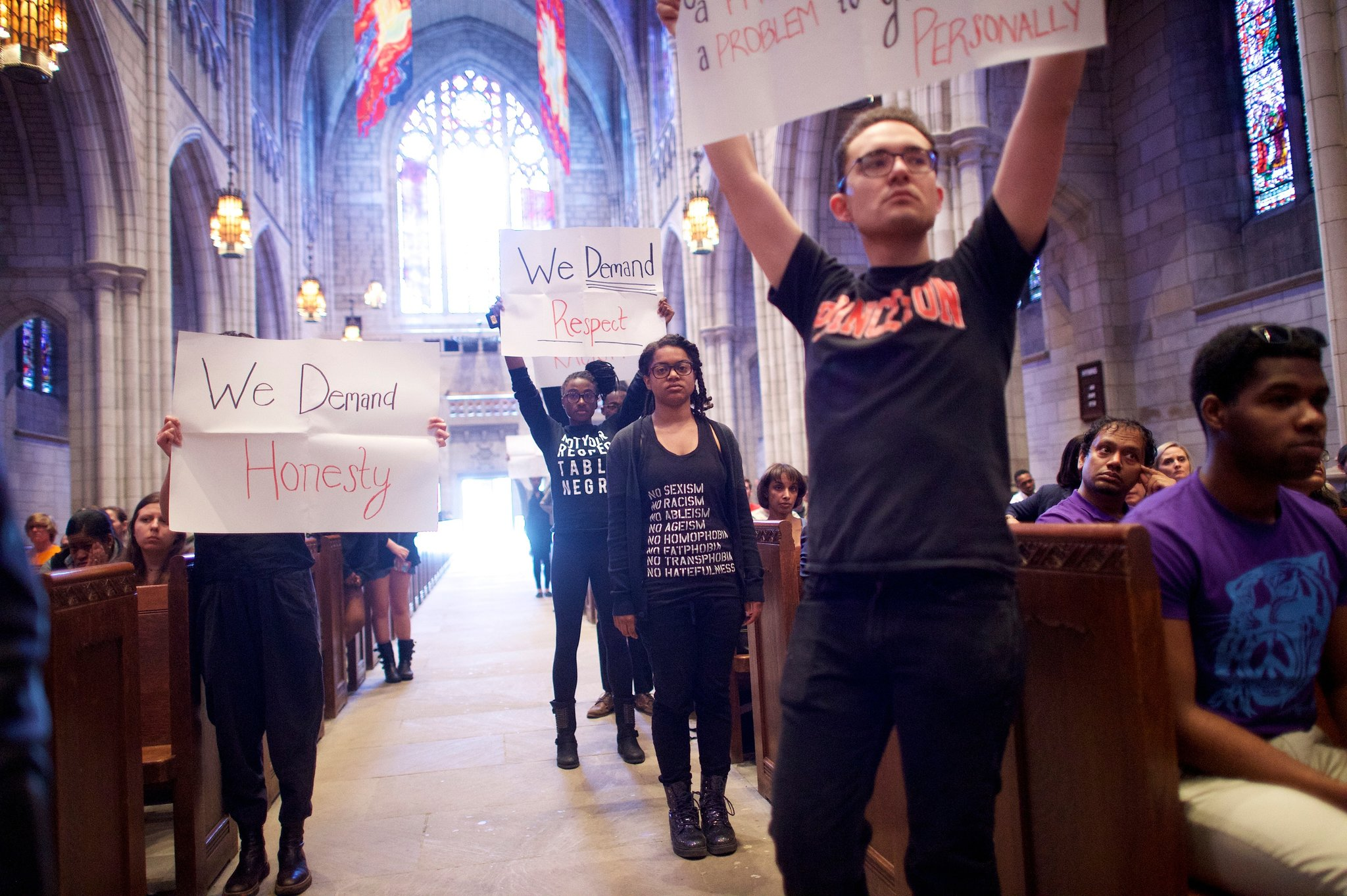 """Students holding signs such as """"We Demand Honesty"""" and """"We Demand Respect"""" during a 2015 demonstration in the Chapel against systemic racism."""