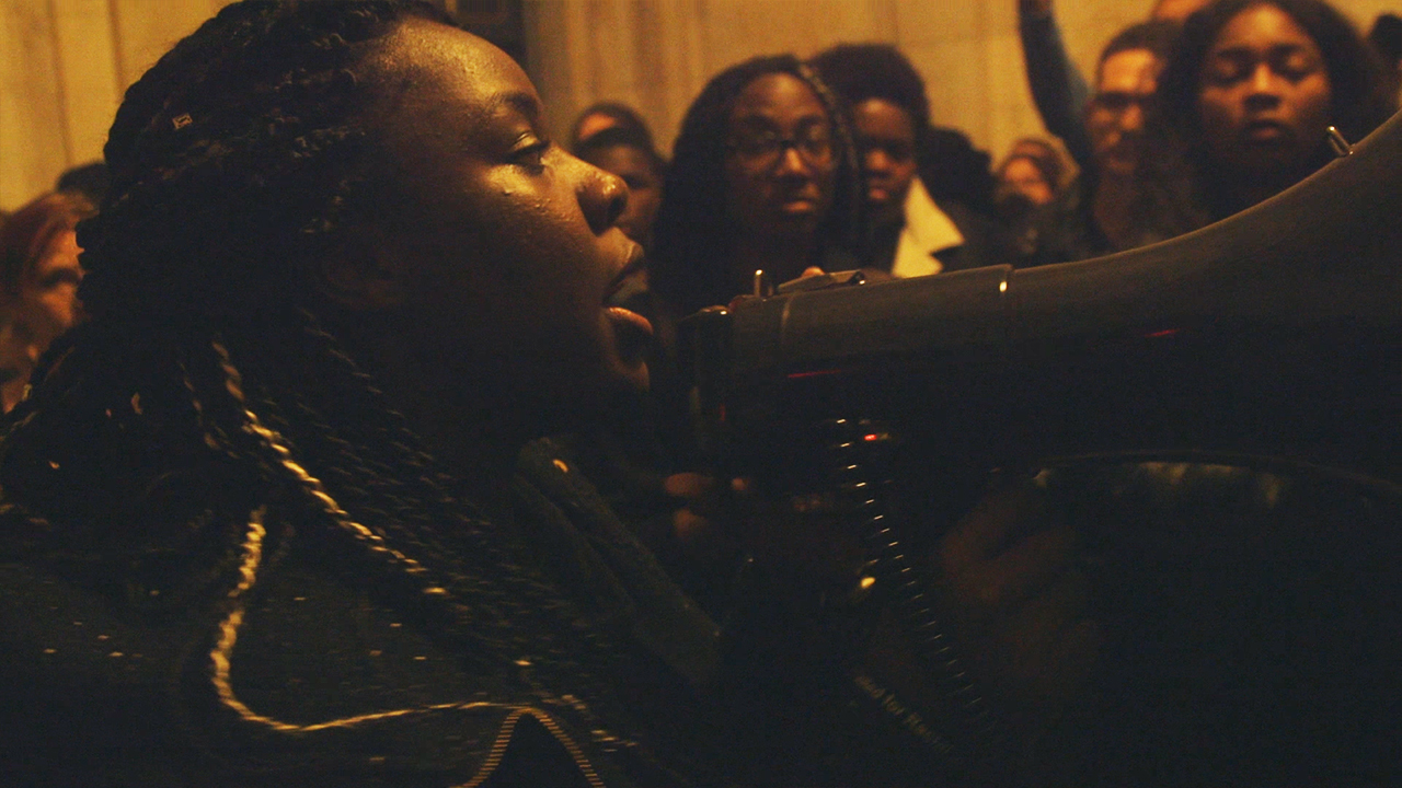 Member of the Black Justice League speaking to a crowd through a megaphone at a protest in 2015.