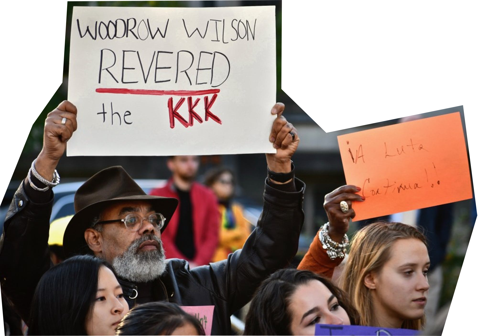 """Community members protesting an installation in front of the Woodrow Wilson School in 2019, with signs such as """"Woodrow Wilson Revered the KKK."""""""