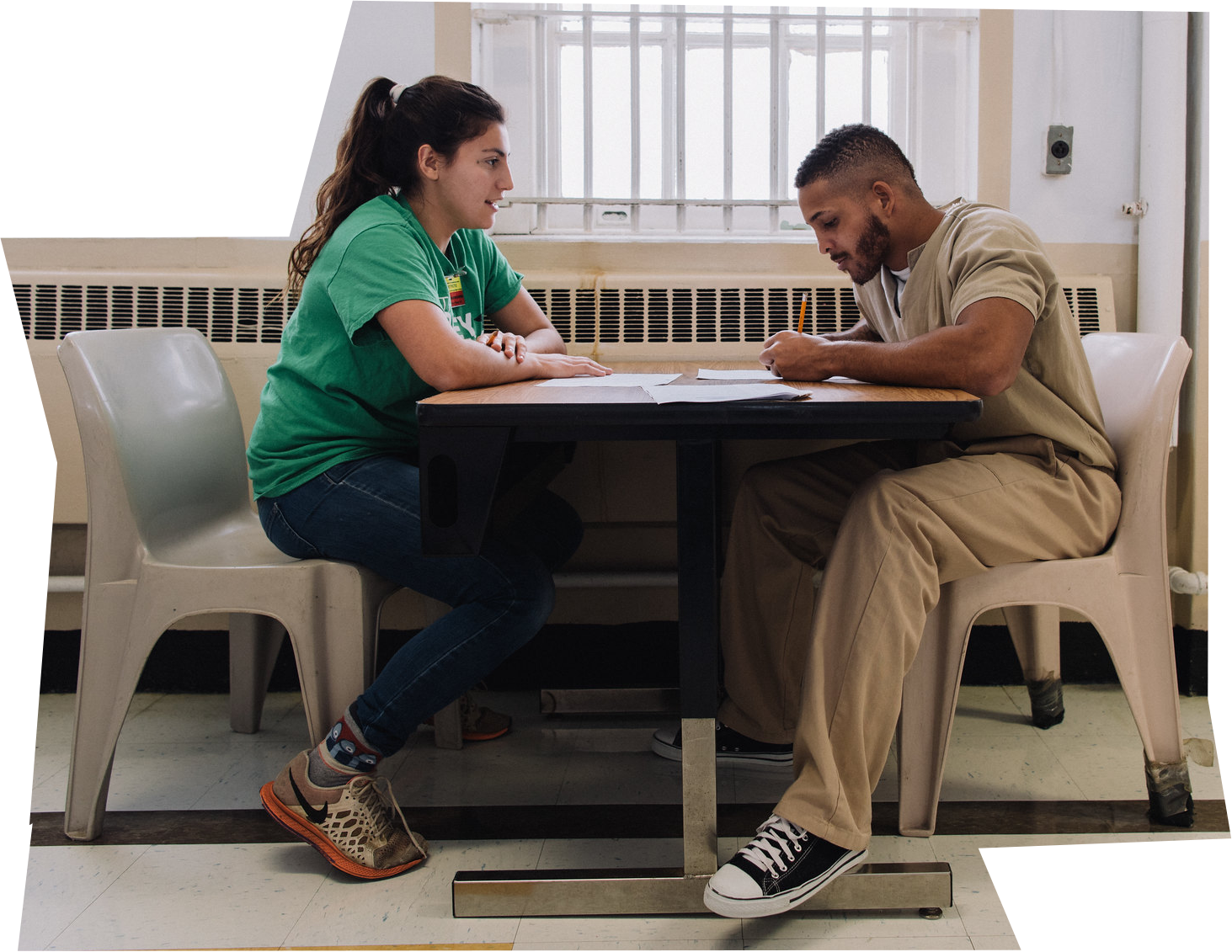 Student sitting at a table across from an inmate at a local correctional facility.